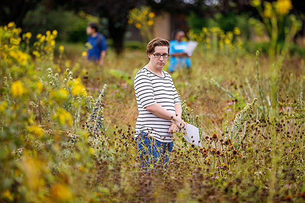 AMBS student Tyler Brinkman stands among the prairie grasses during the Leadership Education in Anabaptist Perspective course.