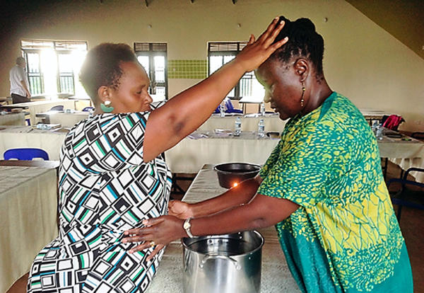 Image: Niwamanya Shallon (at left) and Pamela Obonde anoint each other for healing in the closing ritual of the December 2019 Sister Care/Compassionate Care seminar held in Uganda. (Credit: Esther Muhagachi)