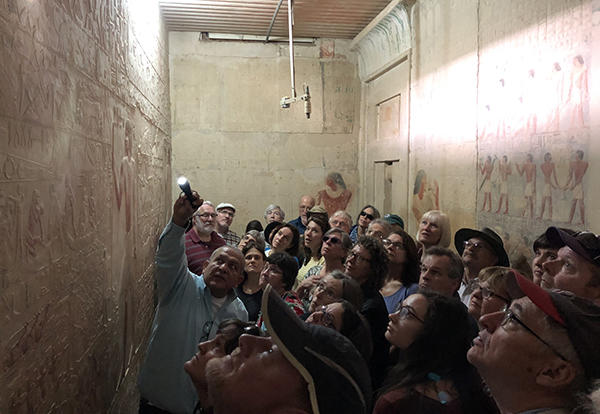 "Participants in AMBS's ""Encountering Egypt"" learning tour listen to Mourad Sedky, an Egyptian tour guide, while gazing at the detailed ancient Egyptian art at the Pyramid of Djoser at Saqqara (27th century B.C.E.). The learning tour is designed to offer o"