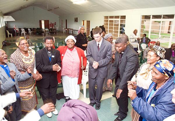 (l. to r.): Amos Sobambela; M.N. Madikane; E.S. Simanga; Olga N.N. Dubula; Joe Sawatzky; Reuben Mgodeli; Mavis Tshandu; Miriam Nompumelelo Dokolwana; and Anna Sawatzky sing and dance at Bethany Bible School in Mthatha, South Africa, in May 2009. (Credit: