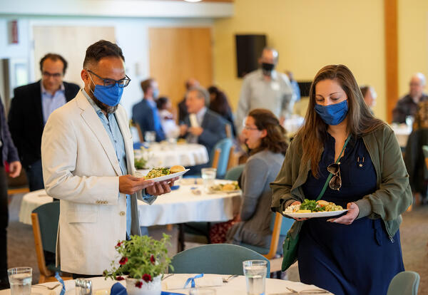 AMBS employees wearing masks, carrying food and getting ready to eat