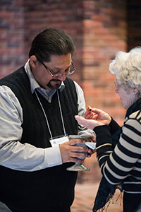 "Pastors Week participants took communion together during worship on Thursday, Jan. 26. ""The more difference we bring, the more fully we experience the presence of the sacred in our midst,"" said worship leader Janeen Bertsche Johnson in opening the time of communion. Above, Byron Pellecer, associate conference minister for Western District Conference, serves communion to participant Lillian Elias. (Credi;y Jason Bryant)"