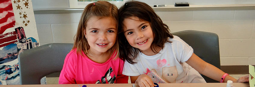 photo of 2 smiling girls in classroom