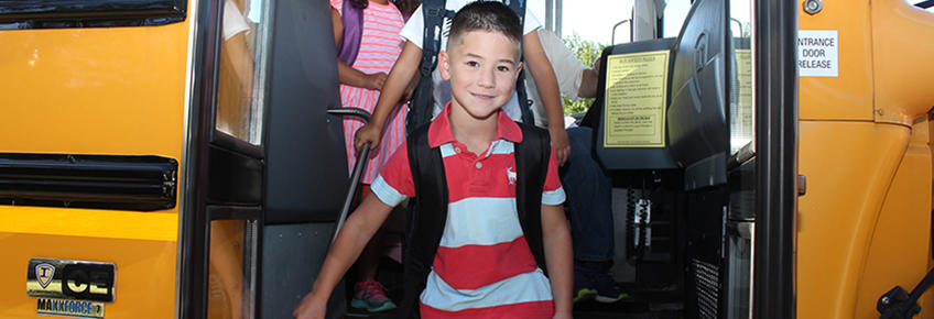 smiling boy exiting a bus