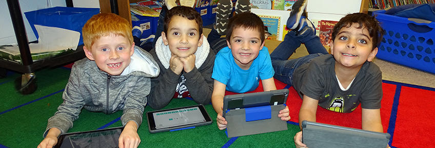 4 smiling students using ipads