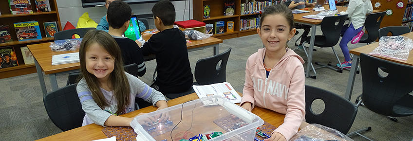 Two smiling girls working in library