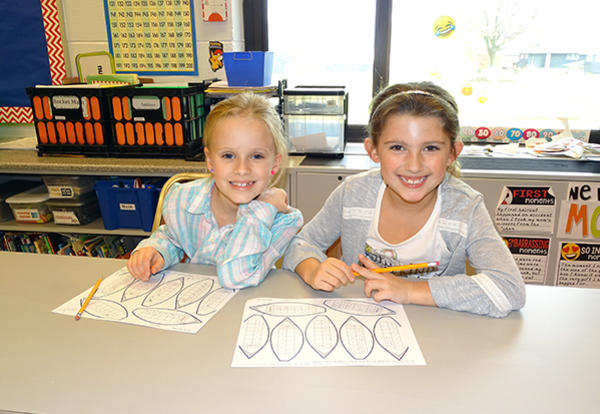 two smiling students working in classroom
