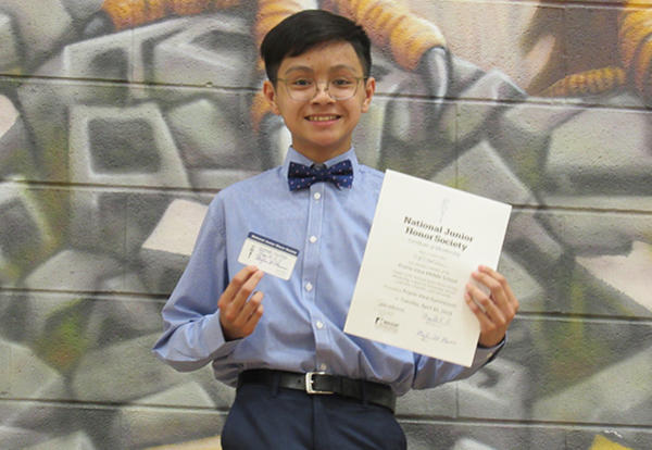 student holding njhs certificate
