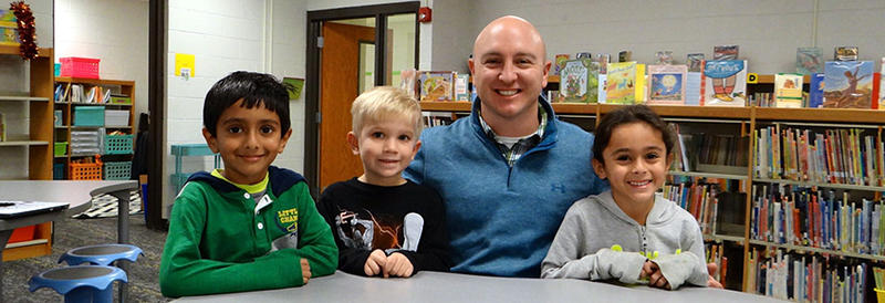 Principal Dan Callaghan with 3 students