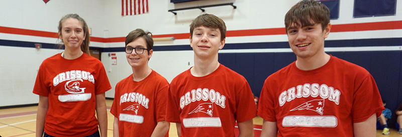 four smiling students in gym class