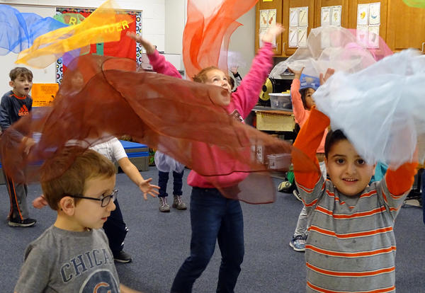 students joyfully playing with scarves