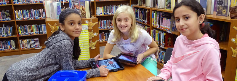 3 smiling students in media center