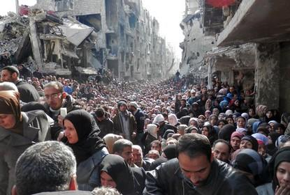 Masses of refugees wait in line to receive food aid