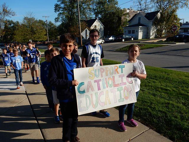Group of St Pets students walking and holding a Support Catholic Education sign