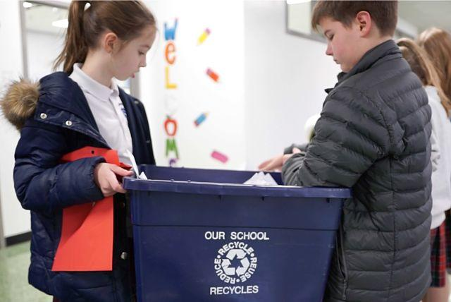 Girl and boy student holding recycling can