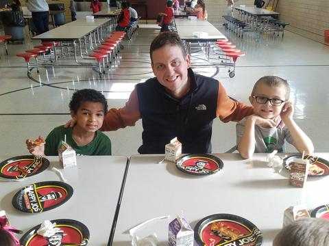 Principal eating with students in lunchroom