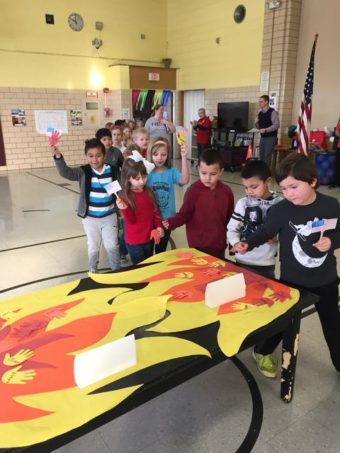 Students making handprints for paper torch