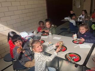 Students in lunchroom eating breakfast with Principal