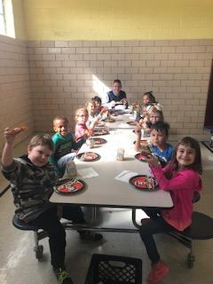 Principal eating Breakfast with students in cafeteria