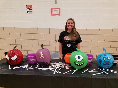 Teacher at table with painted pumpkins