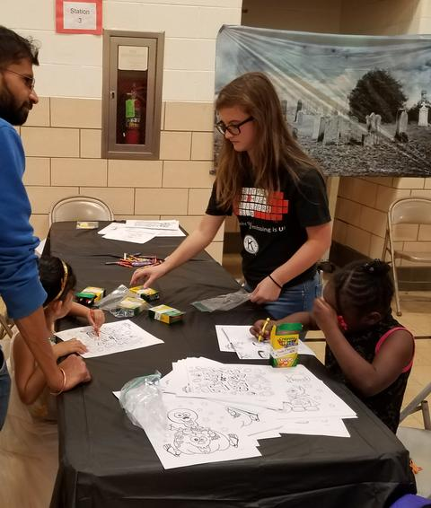 Builder's club student assisting younger student with activities