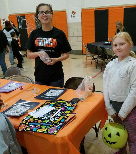 Students with Halloween crafts table