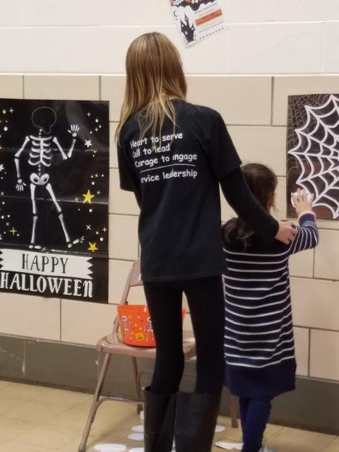 Central Builders Club student assists younger child with games