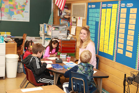 Belle teacher with students sitting at small work table