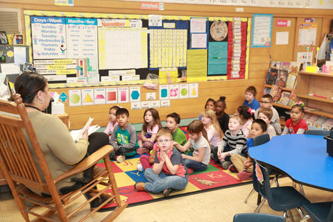 Teacher reading to students from rocking chair