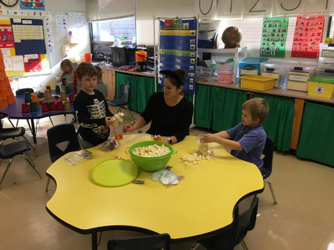 Teacher working with students at large yellow table at Belle