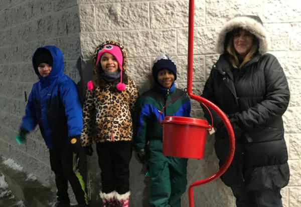 Three Irving Students and teacher in from of Salvation Army Kettle