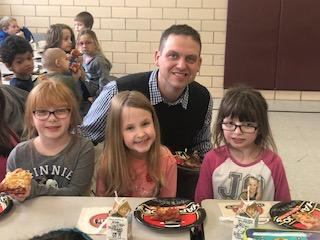 Principal Stabler with three students in lunchroom