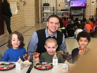 Mr. Stabler with three students eating pizza