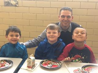Mr. Stabler with three students enjoying pizza party