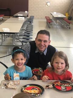 Principal Stabler enjoying pizza with two female students in lunchroom