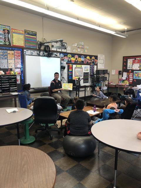 Principal Anderson at desk reading to 4th Graders