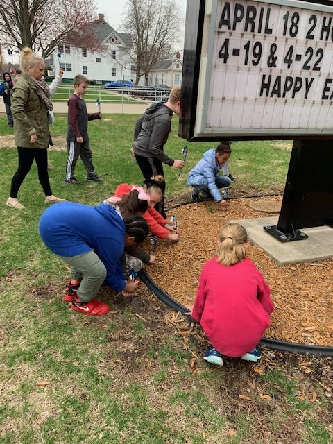 Central Students placing Pinwheels around Central School sign