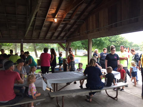 Families enjoying weiner roast at picnic tables