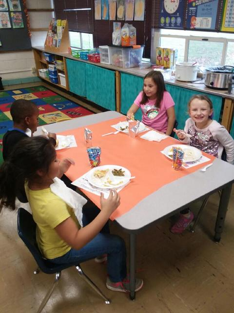 "Three ""Owl"" students eating at table"