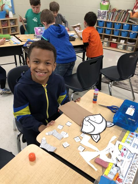 Belle male student making a paper puppet