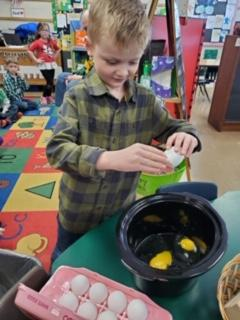 1 male belle student making eggs