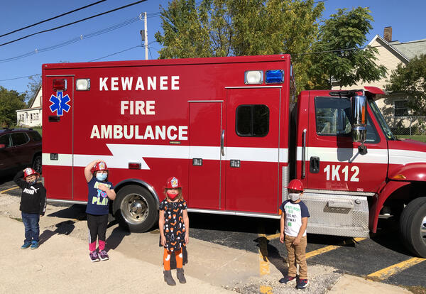 Photo of 4 students standing in front of Ambulance