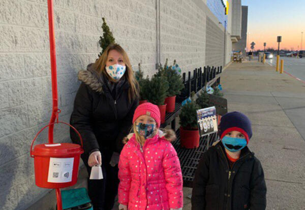 Belle teacher and two students ringing bell for Salvation Army Christmas drive