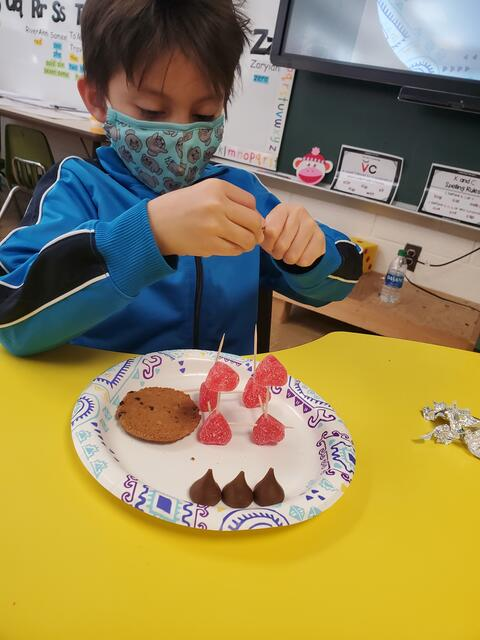 Belle male student working with candy on Valentines Stem project