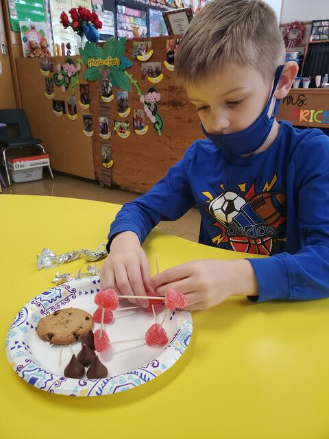 Belle male student working with candy and cookies for Valenties Stem project