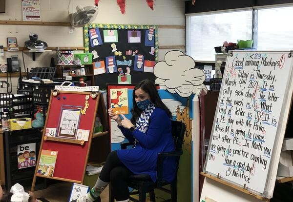 Teacher reading to students with silly socks on