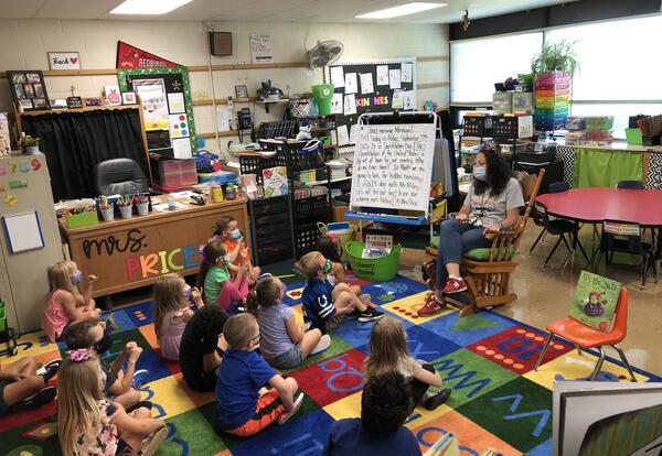 Belle students sitting on floor listening to teacher