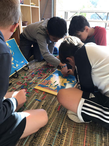 Catcher, Andrew, Juni and Jovan (left to right) work together to complete the pin map of Asia