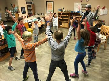 Children form a circle and stretch their arms in the air.