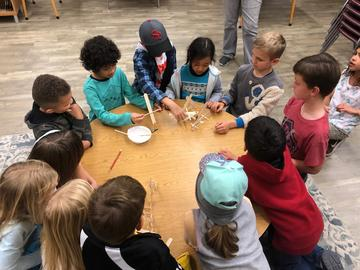 Children work together, at a round table, to create a structure with popsicle sticks.